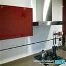 Detalle de mueble vitrina en color rojo burdeos y campana decorativa de líneas rectas en reforma de cocina en barrio de Campanar en Valencia