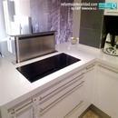 Detalle de campana de extracción escamoteable en mobiliario de cocina con muebles blancos de postformado