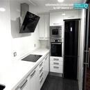 Vista de zona de trabajo en cocina reformada con muebles blancos y electrodomésticos negros realizada en Aldaia Valencia