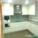 Vista general de la cocina con mobiliario en blanco lacado, electrodomésticos en blanco de la marca Bosch y campana decorativa