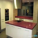 Detalle isla en cocina proyectada dentro de trabajos de construcción de una vivienda en Anna Valencia con mobiliario en blanco y bancada silestone color fucsia
