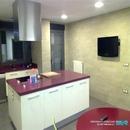Vista general de cocina en Anna con pared realizada con revestimiento rectificado de la marca Saloni