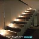 Vista de escalera iluminada desde planta baja con detalle cristal separación