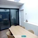 Zona de mesa comedor en doble altura de salón con puerta corredera oculta de entrada a salón-comedor