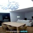 Vista general de salón-comedor con mesa y lampara de diseño en zona doble altura de vivienda
